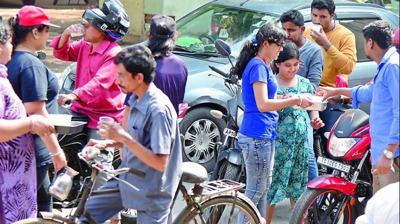 A group of children distributed buttermilk  at Kavadiguda on Sunday. Motorists stopped for the cooling drink, even as the day temperature dipped below the 40ºC mark. (Photo: S. Surender Reddy)