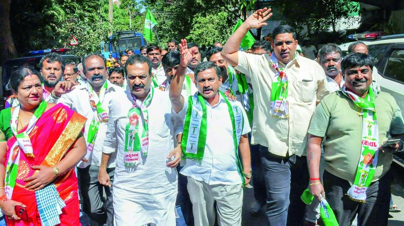 JDS workers protest in front of BJP MLA Ashwath Narayana's residence over his alleged attempts to destablise the government, in Bengaluru, Wednesday. (PTI)