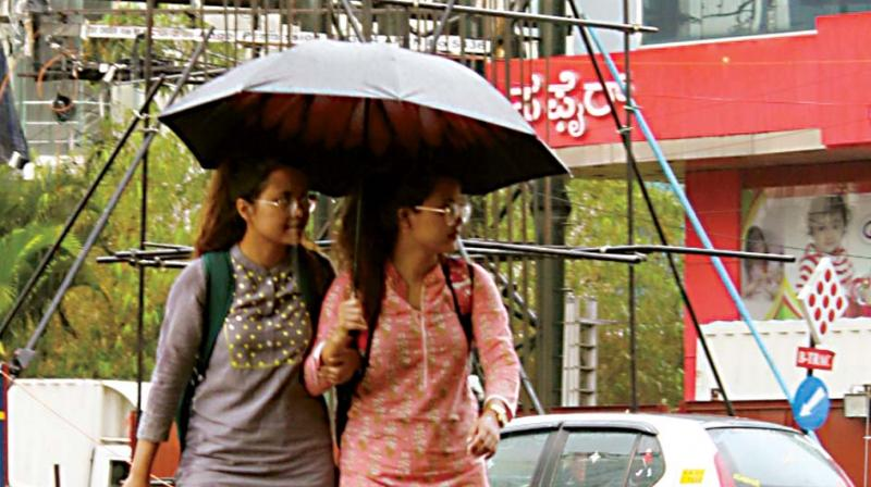 People take out their umbrellas as the city experienced heavy evening showers in Bengaluru on Tuesday. (Image: KPN)