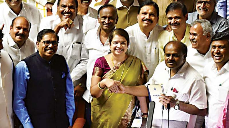 CM H.D. Kumaraswamy with his wife Anitha and Deputy CM  Dr G. Parameshwar after presenting the Budget.  (DC)
