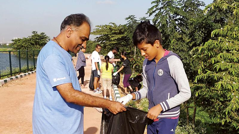 A schoolboy collects waste from Kalkare Lake in Bengaluru on Saturday. (Photo: DC)