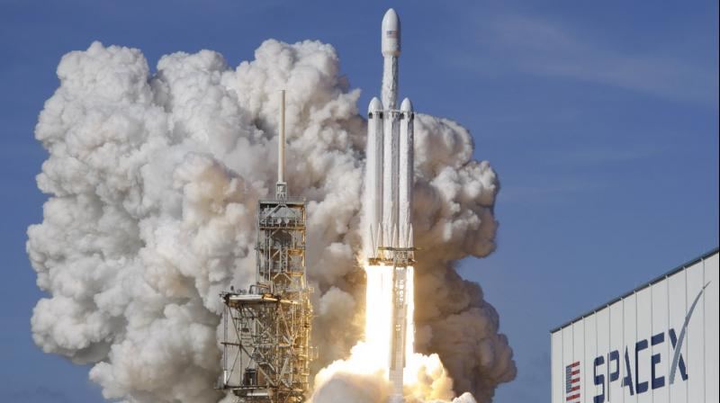 A Falcon 9 SpaceX heavy rocket lifts off from pad 39A at the Kennedy Space Center in Cape Canaveral. The Falcon Heavy, has three first-stage boosters, strapped together with 27 engines in all. (Photo: AP)
