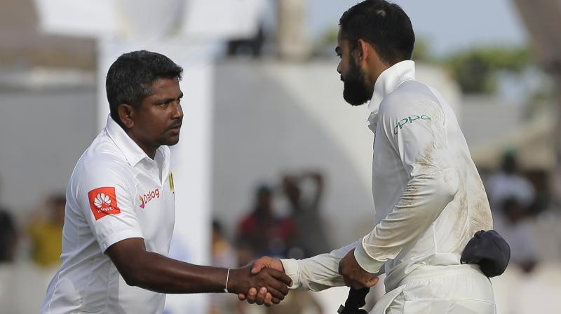 India's captain Virat Kohli, right, shakes hands with Sri Lankan captain Rangana Herath after their win in the first test cricket match in Galle. (Photo: AP)