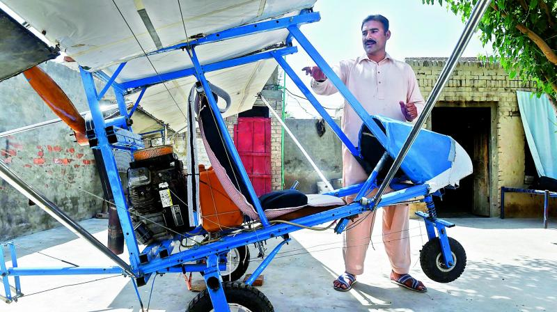Pakistani villager Muhammad Fayyaz stands alongside his small plane at his residence in Tabur village in central Punjab province. It has caught the imagination of the Air Force which apparently gave him a certificate commending his work. — AFP