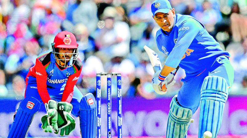 Mahendra Singh Dhoni (right) is watched by Afghanistan's Ikram Ali Khil as he plays a shot during the 2019 Cricket World Cup group stage match between India and Afghanistan in Southampton. (AFP)