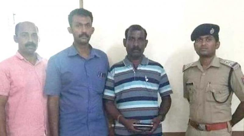 Sunil Kumar (person with purse in his hand) in police custody.