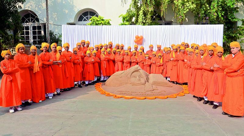 Children dressed as Swamy Vivekananda stand around the sand sculpture on the 155th birth anniversary celebrations at Sri Prakash School in Visakhapatnam on Friday. (Photo: DC)