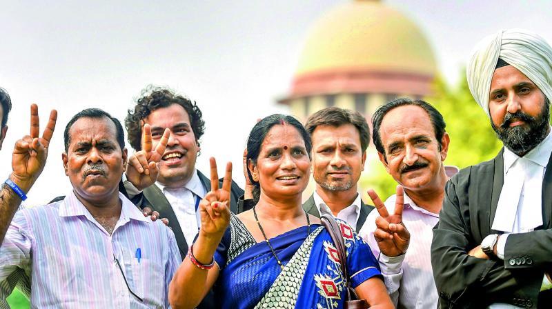 Dec. 16 gangrape victim's parents show victory sign after the Supreme Court's verdict in New Delhi on Monday. (Photo: PTI)