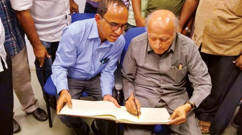 Prof. M.S. Swaminathan signs a guestbook at St. Joseph's College in Bengaluru on Monday —DC