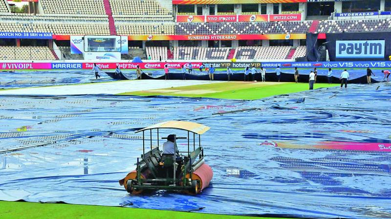 The groundsmen cover the Hyderabad pitch as rain lashes the city.  (Photo: P. Surendra)