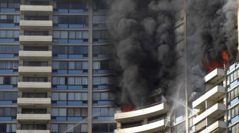 Smoke billows from the upper floors of the Marco Polo apartment complex in Honolulu (Photo: AP)