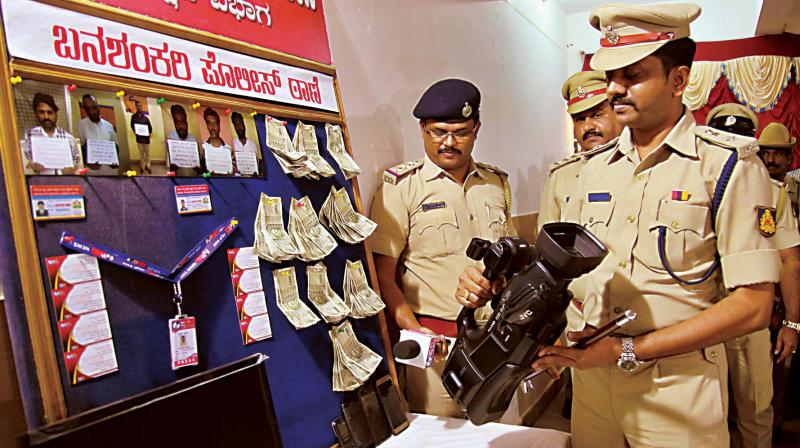 DCP (South) Sharanappa with a fake scribe's ID Card and camera during the property parade and press conference at his office in Bengaluru on Thursday (Image DC)