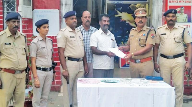 RPF personnel hand over a bag containing Rs 81,000, Aadar card and important documents to a passenger who misplaced his bag while travelling on a train from Trichy to Chennai. (Photo: DC)