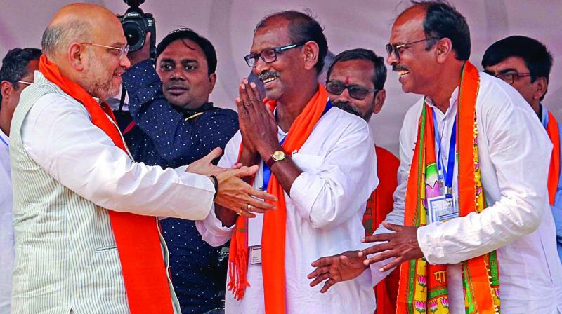 BJP president Amit Shah meet party candidates D.K. Mondal (Birbhum) and Ramprasad Das (Bolpur) during a rally in Ganpur, Birbhum district of West Bengal, on Monday.  (PTI)