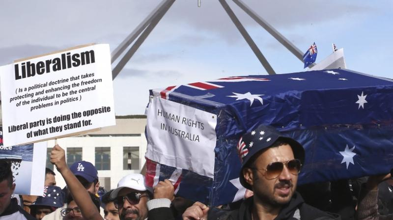 Protestors hold up a placard and a symbolic coffin during a refugee protest at Parliament House in Canberra, Australia, Monday, July 29, 2019. (Photo: AP)