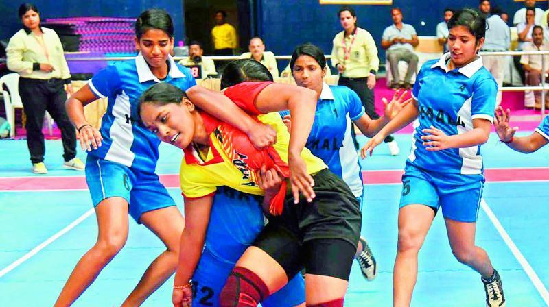 Kerala women players trap Andhra raider (centre) in their pre-quarterfinal of 65th Senior National Kabaddi Championship at the GMC Balayogi Stadium in Gachibowli, Hyderabad. Kerala won 31-21.