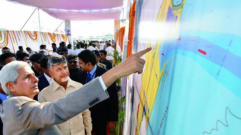 Navayuga Constructions chairman Visweswara Rao briefs Chief Minister N. Chandrababu Naidu on the Machilipatnam port works, in Krishna district on Thursday. (Photo: DC)