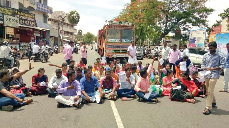 Applicants for the direct recruitment for computer instructor-grade one sit on a dharna, blocking vehicular traffic on the Tiruchengode-Erode highway. (Photo: DC)