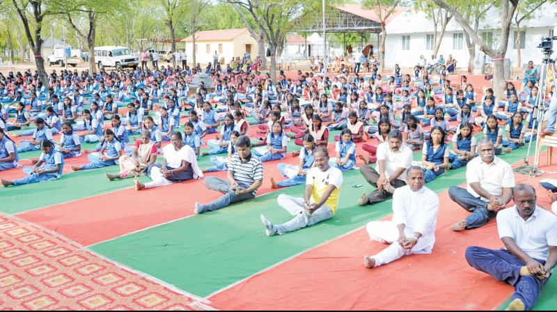 A. Annadurai, Thanjavur district collector and M. Balasubramoniam, Director, SZCC, perform yoga alongwith thousands of students at Thanjavur on Friday. (Photo: DC)
