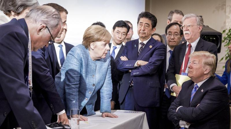 Her fists planted on the table, she looms above an apparently nervous Trump, looking up at her and listening without response. (Photo: AP)