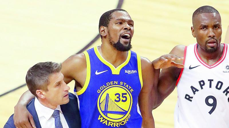 Kevin Durant (centre) of the Golden State Warriors is assisted off the court after sustaining an injury during Game Five of the NBA Finals against the Toronto Raptors in Toronto, Canada, on Tuesday. (Photo: AFP)