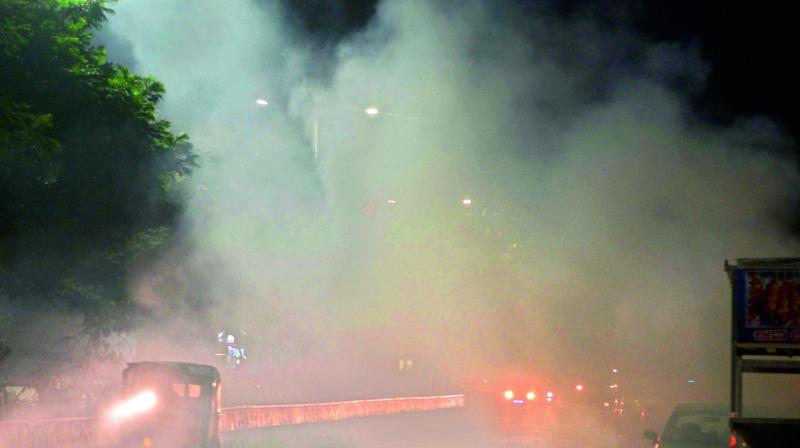 A file photo of burning garbage on the road blocking visibility in Vijayawada.