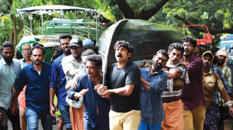 A group of fisher folks carrying a country boat for rescue operations at Paravur on Sunday.  (Photo:DC FILE)