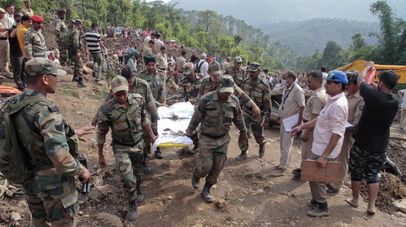 Army soldiers and rescue workers recover bodies of landslide victims even as they try to pull out two buses that were covered in mud after a landslide triggered by heavy monsoon rain in Urla village, Himachal Pradesh. (Photo: AP)