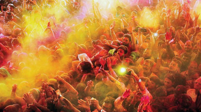 Devotees play with 'gulal' on the occasion of Holi at Govind Dev Ji temple in Jaipur on Thursday. (Photo: PTI)