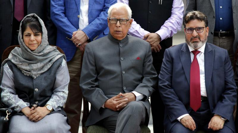 J&K Governor N N Vohra with Chief Minister of J&K Mehbooba Mufti with the new minister Syed Altaf Bukhari poses for a photograph during a swearing in ceremony at the Governor House in Jammu. (Photo: PTI)