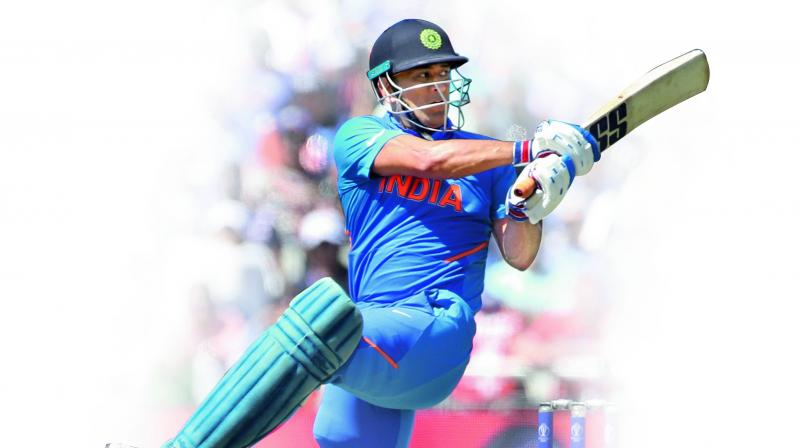 Mahendra Singh Dhoni plays a shot on way to his half-century against West Indies in their group stage match at Old Trafford in Manchester on Thursday. (Photo: AP)