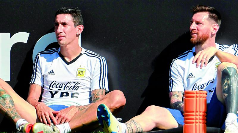 Argentina players Angel Di Maria (left) and Lionel Messi rest during a training session in Rio de Janeiro. (Photo: AFP)