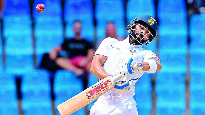 Virat Kohli takes evasive action during the first day of the Test against West Indies at Vivian Richards Cricket Stadium in North Sound, Antigua, on Thursday. (Photo: AFP)