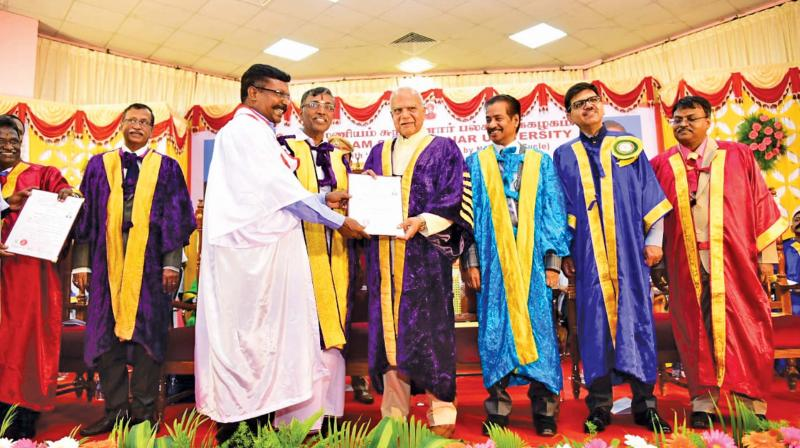 VCK president and LS member Thol Thirumavalavan recieves PhD from state governor and chancellor of the university, Sri Banwarilal Purohit. (Photo: DC)