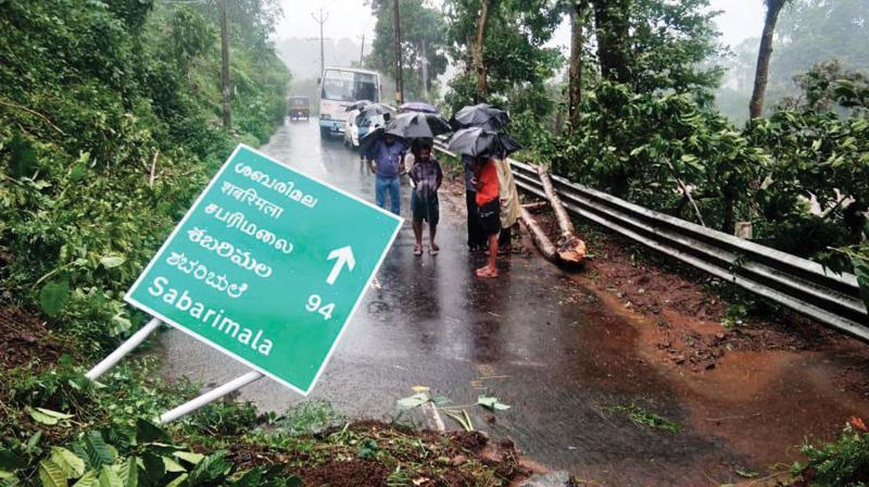 People gather near a landslide site at Chappath near Upputhara in Idukki district on Sunday following heavy rains in the state. Traffic was partly affected in many areas on account of the landslide. (Photo: BY ARRANGEMENT)