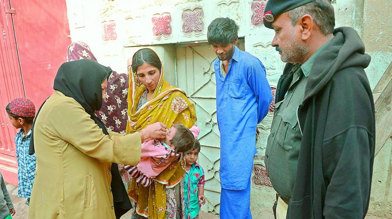 Pakistani health administer gives Polio drops to an infant.