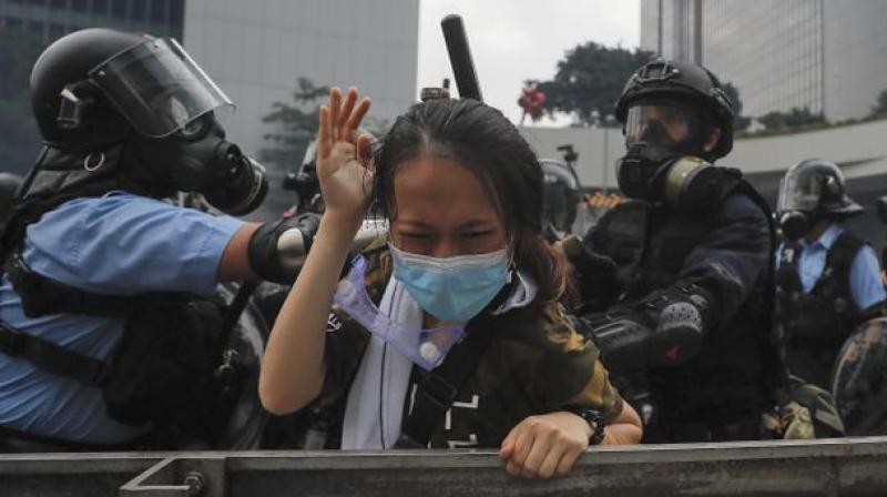 A protester reacts as she tackled by riot police during a massive demonstration outside the Legislative Council in Hong Kong, Wednesday, June 12, 2019. Hong Kong police have used tear gas and high-pressure hoses against thousands of protesters opposing a highly controversial extradition bill outside government headquarters. (Photo: AP)
