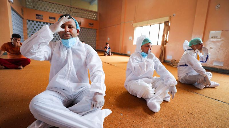 Health workers wear protective suits along with patients perform yoga ahead of International Yoga Day, at Covid Care Centre in Jammu. (Photo: PTI)