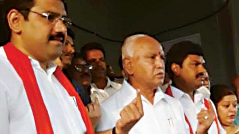 State BJP chief B.S. Yeddyurappa with his sons Raghavendra, party candidate, and Vijayendra after casting their votes in Shivamogga on Tuesday	(Photo: DC)