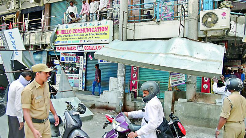 The GHMC officials remove half of banners from three buildings at Dharam Karamroad in Ameerpet on Tuesday. (Photo: S. Surender Reddy)