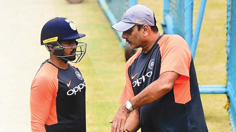 Karun Nair is all ears to coach Ravi Shastri during a training session in Bengaluru on Monday