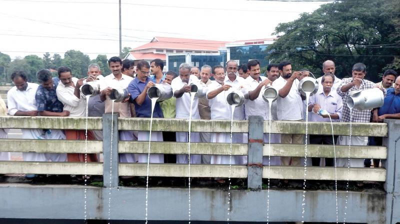 Farmers under Kerala Aggressive Dairy Farmers Association pour milk from over Muvattupuzha bridge protesting against low procurement price of milk on Monday (Photo: DC)