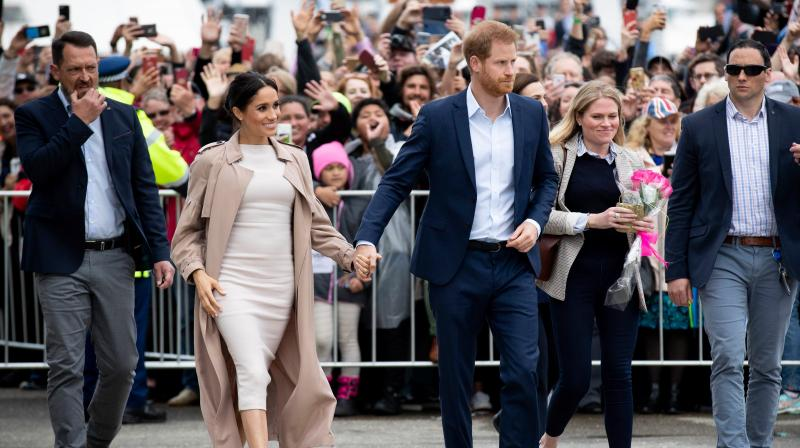 Britain's Prince Harry (C) and his wife Meghan, Duchess of Sussex (2nd L) meet well-wishers during a public walk along the Viaduct Harbour in Auckland on October 30, 2018. (Photo: AFP)