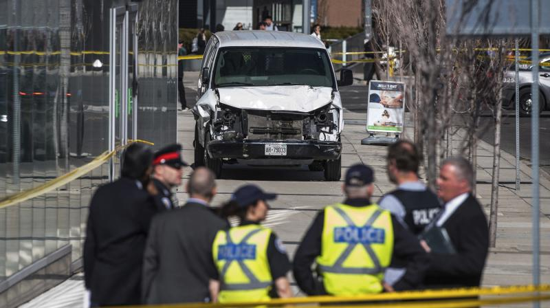 Police seen near a damaged van after a van mounted a sidewalk crashing into pedestrians in Toronto on Monday. (Photo: AP)