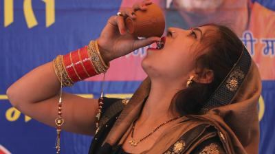 A woman does bottoms up at a gau mutra party organized by the All-india Hindu Mahasabha to publicise cow urine as a cure for the coronavirus pandemic sweeping the world. (AP)