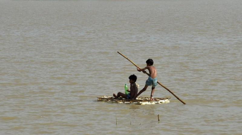 Children use a raft to travel over flood waters in Araria in Bihar on August 19, 2017. (Photo: AFP)
