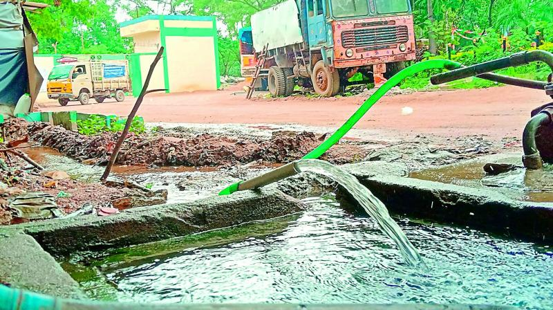 Despite being a holiday on Saturday, water is pumped into the open tank which is seen overflowing at the GHMC circle office in Quthbullapur.
