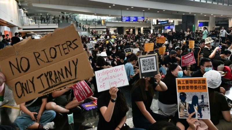 On Friday visitors were greeted by a sea of black-clad protesters chanting anti-government slogans, holding banners and handing out flyers. (Photo: AFP)