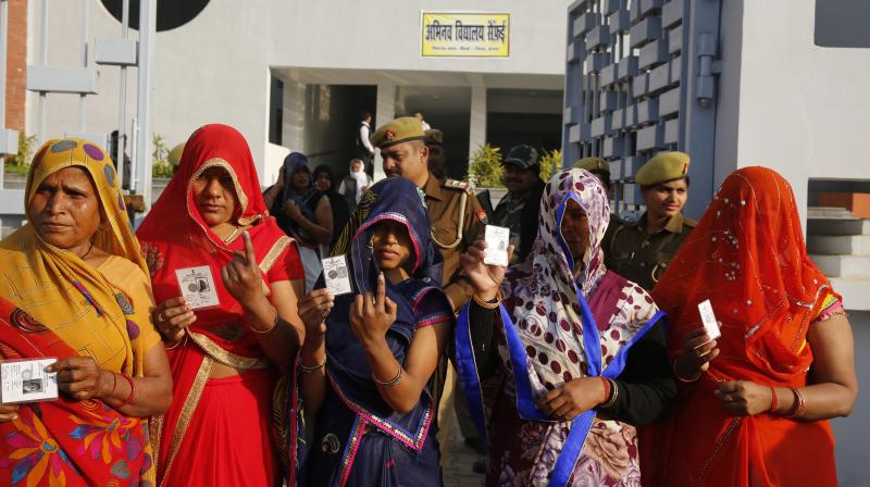 Indian women show their index finger marked with indelible ink after casting their vote at a polling station in Saifai, Etawah, Uttar Pradesh, on Sunday. (Photo: PTI)