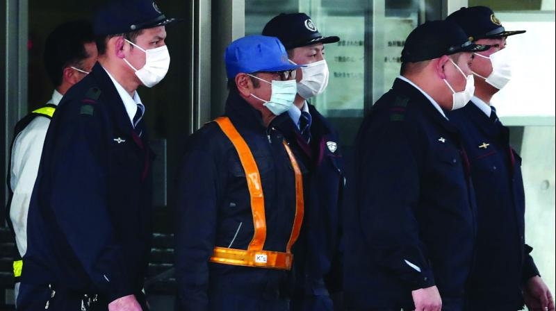 Ousted Nissan chief Carlos Ghosn, wearing a blue cap, is escorted out of the Tokyo Detention House in Tokyo on Wednesday